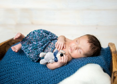 dream body: newborn boy sleeping on little cot with toy mouse Stock Photo
