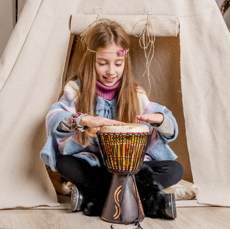 interior decor: little girl with drum near wigwam playing Indian close-up Stock Photo
