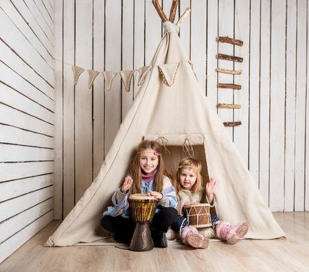tambor: sonriendo niñas que juegan los tambores cerca de tienda india como los indios