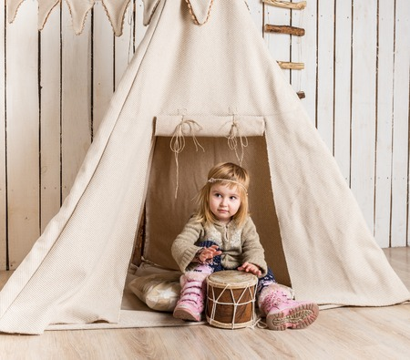 wigwam: little girl with drum near wigwam playing Indian
