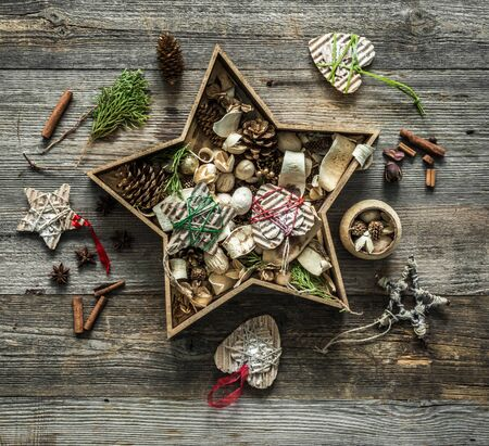 star shaped: christmas decorations in a star shaped box on wooden background