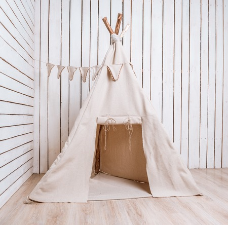 tent: wigwam for children in a room with wooden planked walls Stock Photo