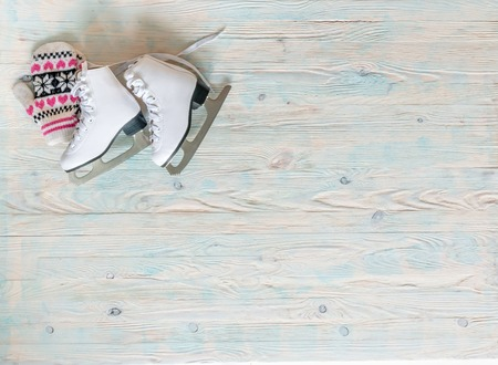ice skates with mitten on wooden background with text space top view Stock Photo
