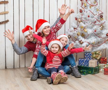 familj: stor familj i röda Santa hattar nära faux julgran i studio Stockfoto