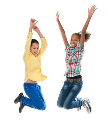 saltando: ni�o y ni�a con diferente complexi�n saltando aislados sobre fondo blanco