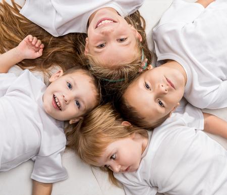 niños sonriendo: niños sonrientes que mienten con las cabezas juntas aisladas sobre fondo blanco
