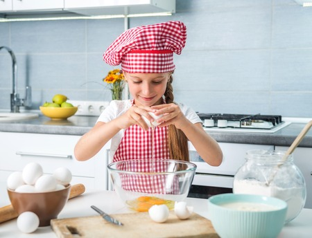 little girl breaking eggs into a glass bowl preparing a dough