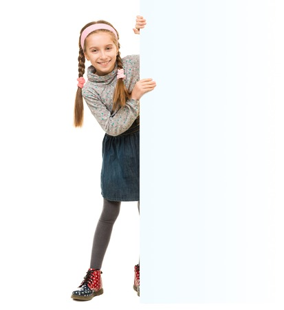 denim skirt: cute little girl peeking out from behind an empty blank for ad isolated on white background