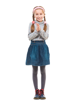 denim skirt: cute little girl standing and rubbing her hands isolated on white background