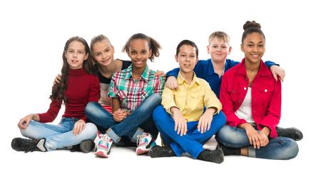 niños sentados: amigos adolescentes que se sientan en el suelo abrazando mutuamente aisladas sobre fondo blanco
