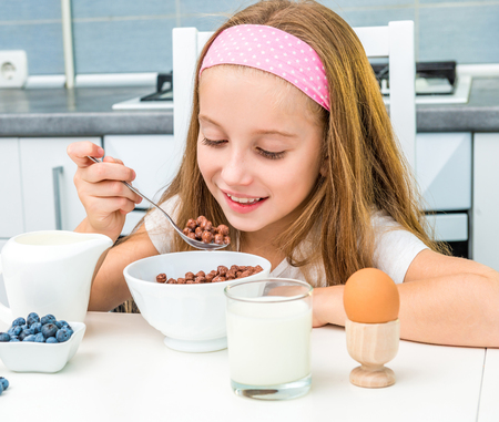 chocolate balls: little girl eating chocolate balls for breakfast
