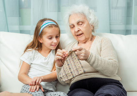 the great grandmother: ganddaughter learning to embroider with granny on sofa