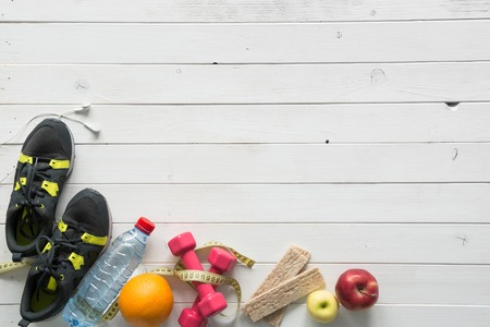 fitness items on wooden planks background top view with text space