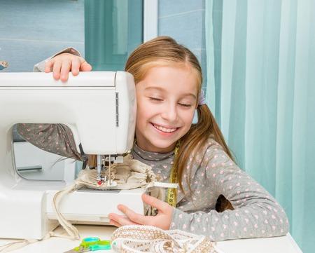 coser: una sonrisa de niña en la mesa con la máquina de coser que mira la cámara Foto de archivo