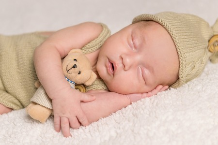 yoy: sweet newborn baby sleeping in costume and hat with teddy-bear