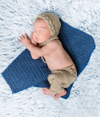blue blanket: top view of a newborn baby in costume lying on blue blanket