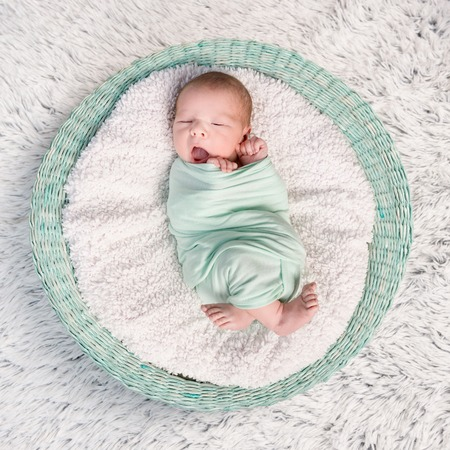 nappy: sweet newborn wrapped in a nappy sleeping on a round rug top view