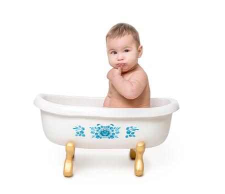 bebé divertido que se sienta en baño poco aislado en el fondo blanco Foto de archivo