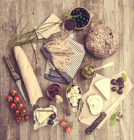 food and wine: Cheese, wine and other food  ingredients on a wooden table. French snacks on a wooden background.