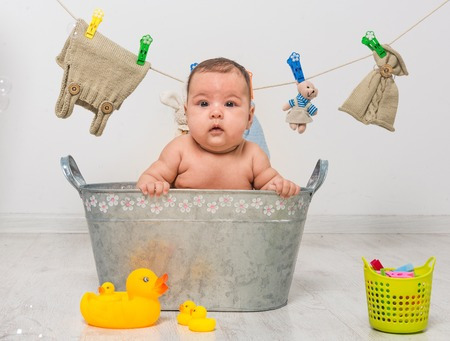 'young things': little two-month girl bathes in a  trough and dry her clothes Stock Photo