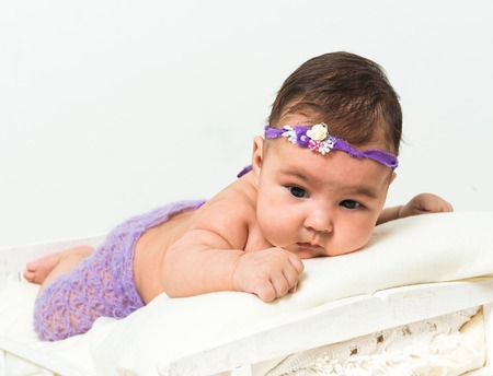 0 3 months: two-month-old girl in fishnet panties lying in bed