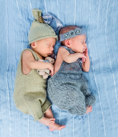 0 6: newborn twins  sleeping with toys on a blue blanket Stock Photo
