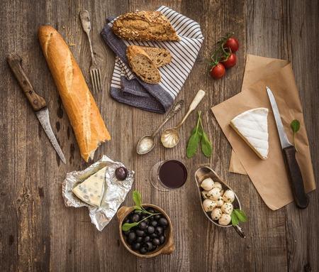pasteleria francesa: Cocina franc�s. Diferentes tipos de queso, el vino y otros ingredientes en una mesa de madera