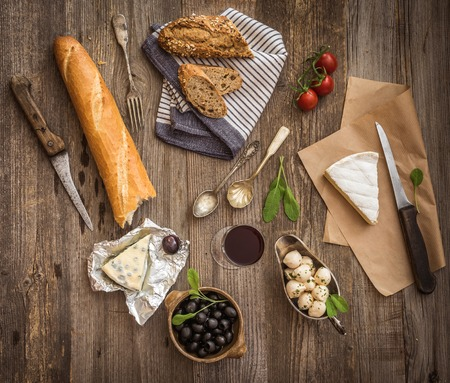 french: French cuisine. Different types of cheese, wine and other ingredients on a wooden table