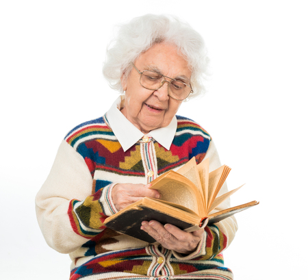great grandmother: elderly woman flipping an old book isoalted on white background Stock Photo