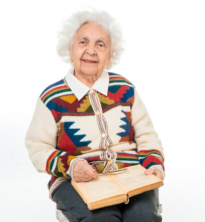 white headed: elderly woman flipping an old book isoalted on white background Stock Photo