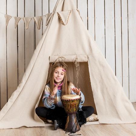 wigwam: little girl with drum near wigwam playing Indian