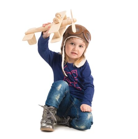 kids hand: cute little girl in pilot hat with wooden plane in hand isolated on white background Stock Photo