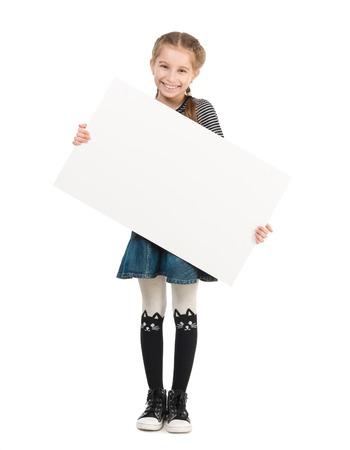 hoja en blanco: muy sonriente colegiala con la hoja en blanco en las manos aisladas en el fondo blanco