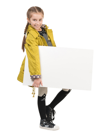 kids background: smiling little girl in coat with blank sheet in hands isolated on white background