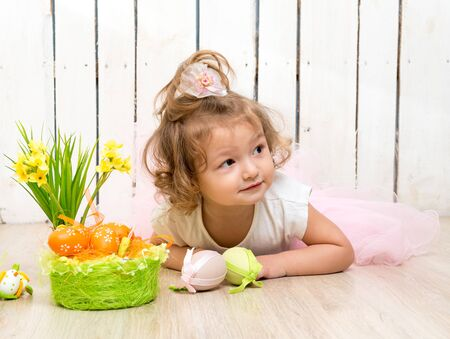 camera girl: funny little girl lying on the floor with easter decorations and looking at camera