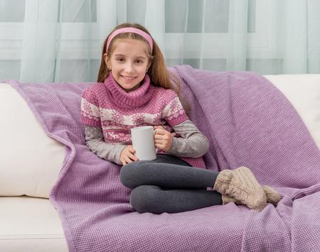 sueter: preciosa niña en un sofá con manta caliente que sostiene una taza de té Foto de archivo