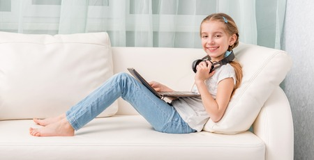 girl legs: smiling little girl listening something with headphones and note book on sofa looks at camera