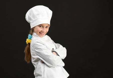 children background: little smiling girl in white chef costume with rolling pin in hand isolated on black background Stock Photo