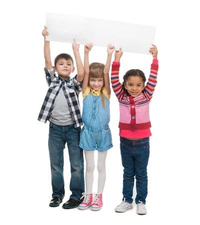 niños felices: tres niños que sostiene la hoja de papel en blanco aislado en el fondo blanco
