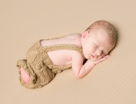 overalls: lovely newborn baby in knitted overalls sleeping on his stomach