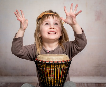 cute little girl with headband playing drum on the floor Standard-Bild