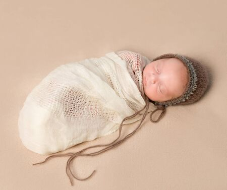 swaddled: beautiful sleepy swaddled newborn baby in knitted hat Stock Photo