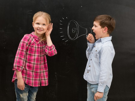 hands covering ears: little boy shouting in drawn on the blackboard mouthpiece and little girl covering her ears with her hands Stock Photo
