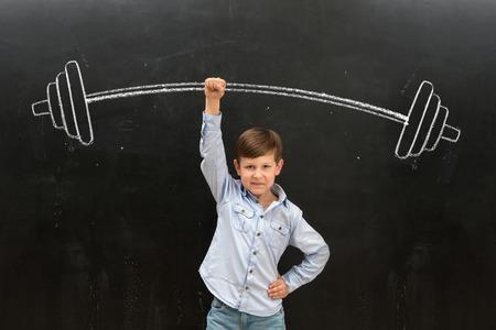 easily: cute little boy easily rising drawn on the blackboard barbell on finger Stock Photo