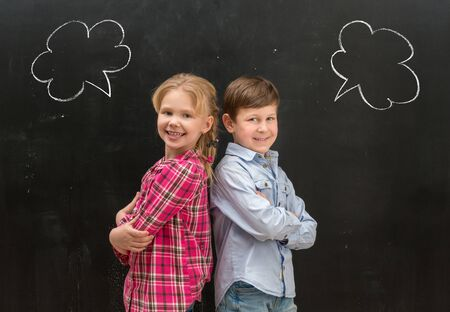 phrase: two little smiling children standing back to back with phrase clouds drawn on the blackboard