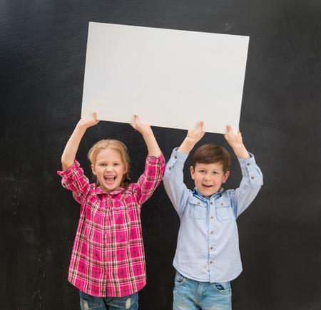 niños riendose: dos niños pequeños ríen de mantenimiento de la hoja de papel en blanco encima de sus cabezas