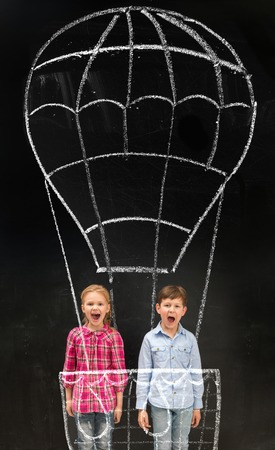 schoolchildren: two laughing little schoolchildren flying on imaginary drawn air baloon on the blackboard Stock Photo