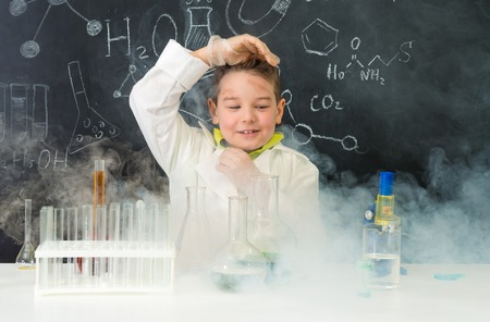 laboratory research: pop-eyed funny boy after chemical experiment in chemistry lab with fume Stock Photo