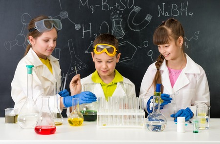 three little students on chemistry lesson in lab doing an experiment Фото со стока