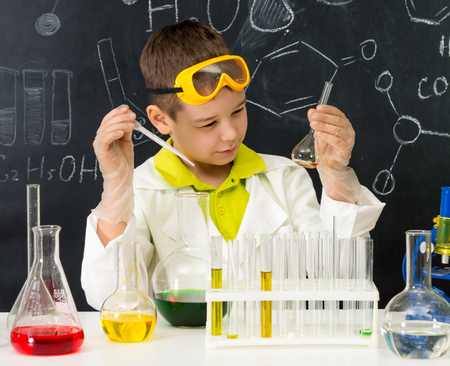 doing: schoolboy  gown and gloves watching chemical experiment in tube in chemistry lab Stock Photo